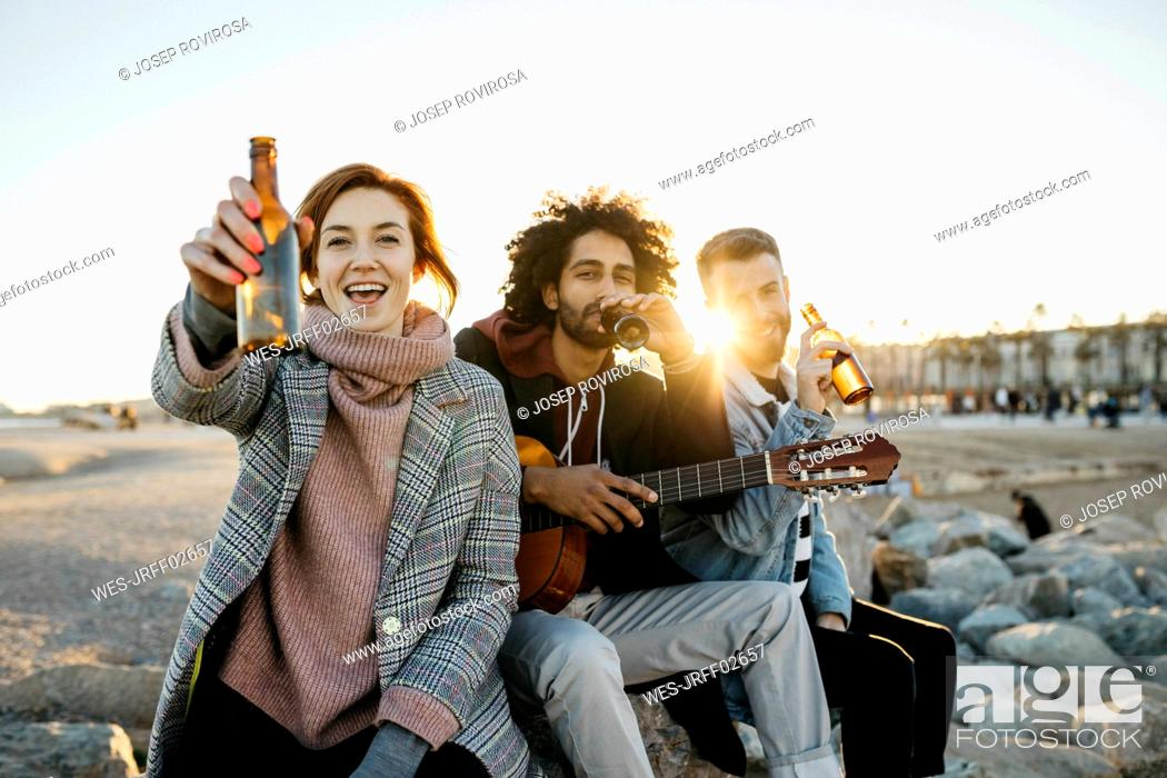 Imagen: Three happy friends with guitar toasting beer bottles at sunset.