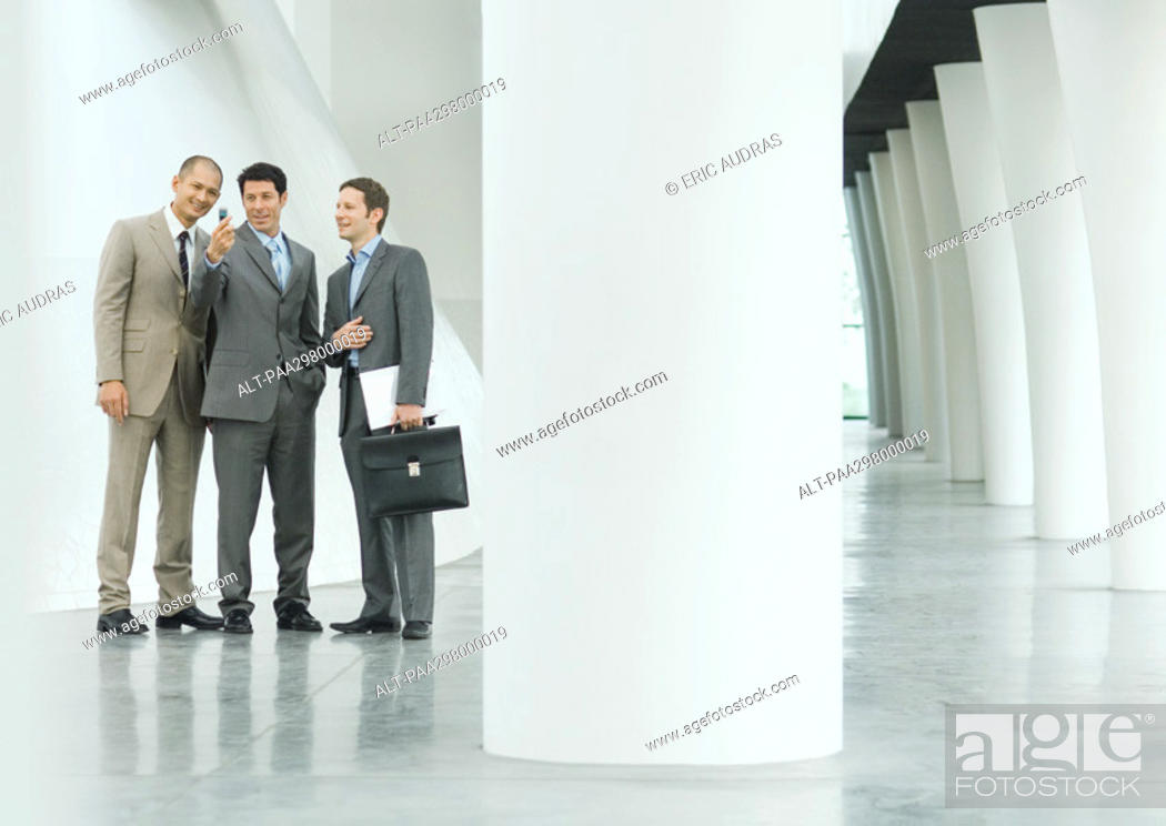 Stock Photo: Three businessmen looking at cell phone in lobby.