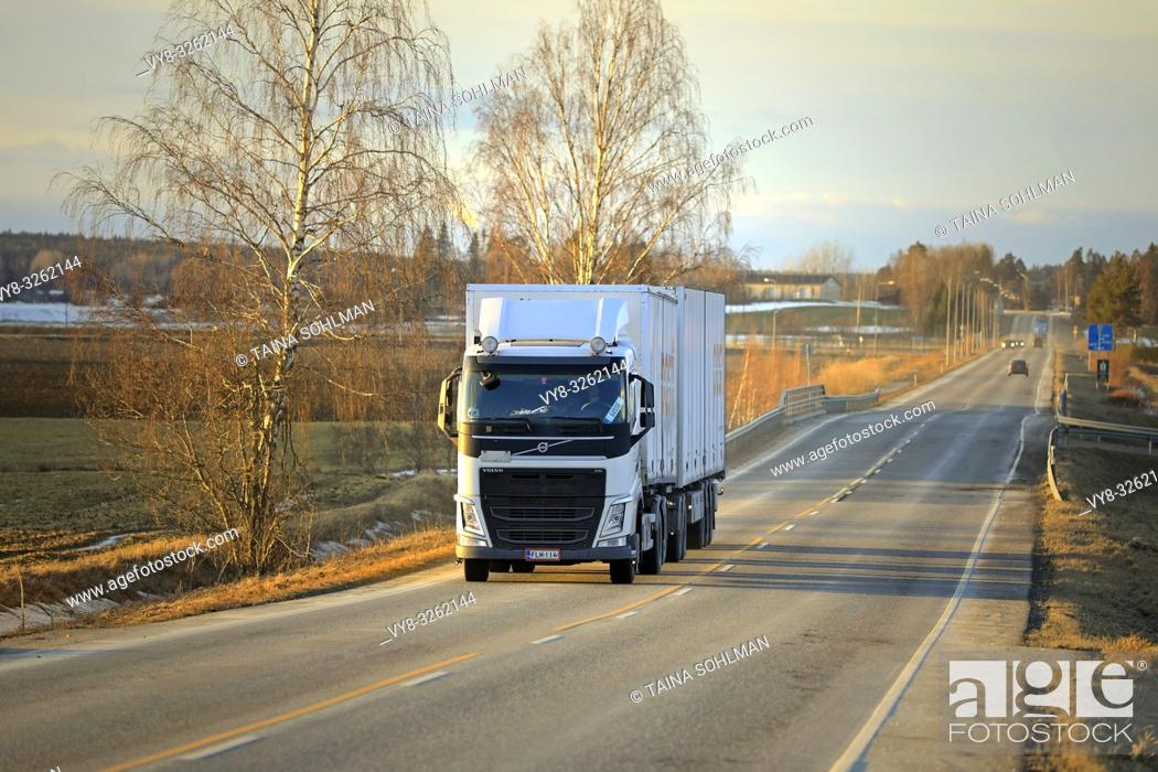Stock Photo: Salo, Finland - March 1, 2019: White Volvo FH truck double trailer for Posti Group, Finnish postal service on highway at sunset time in early spring.