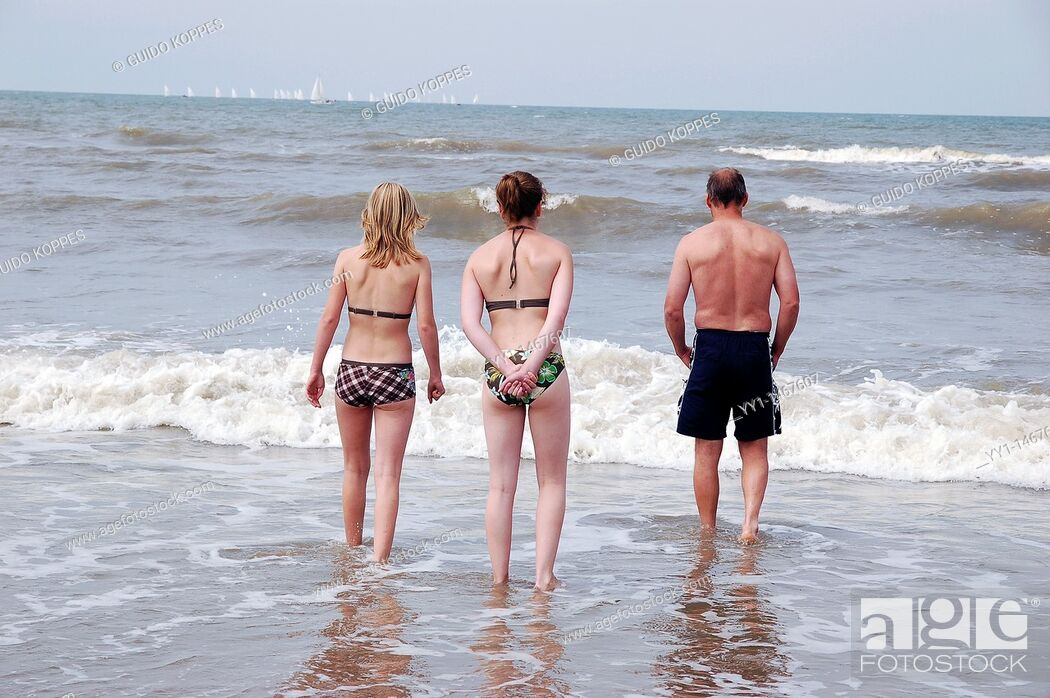 Stock Photo: Scheveningen, Netherlands. Three people in swimsuits walking into the salty water of the North Sea for a swim.