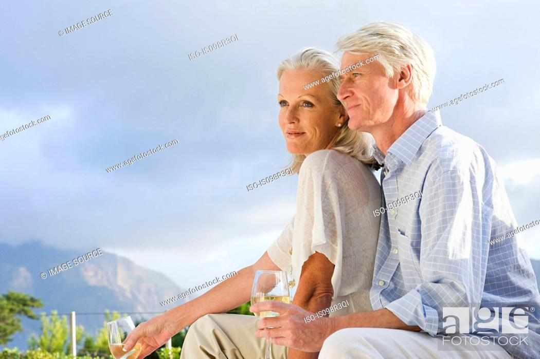 Stock Photo: Middle aged couple relaxing outside with glasses of wine.