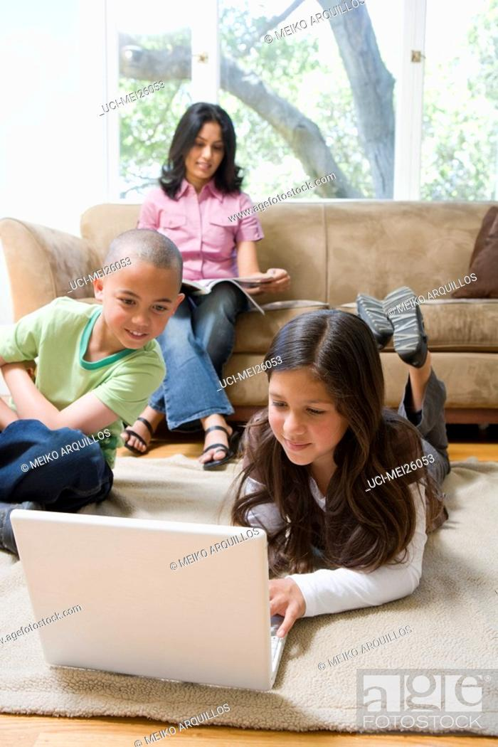 Stock Photo: Siblings using a laptop in living room.