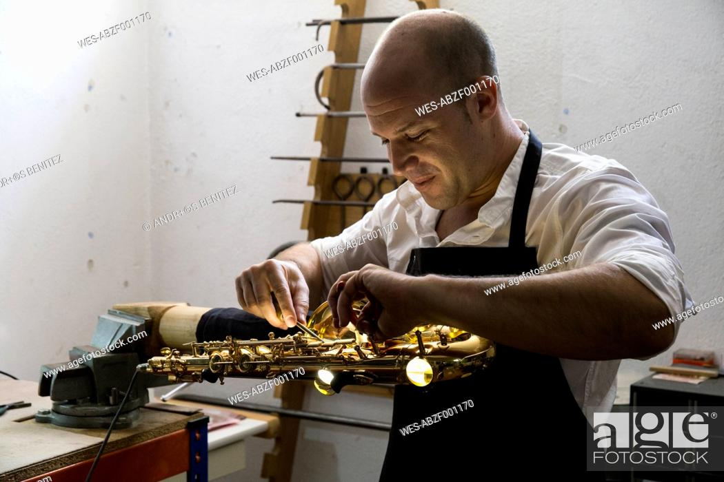 Stock Photo: Instrument maker dismounting a saxophone during a repair.