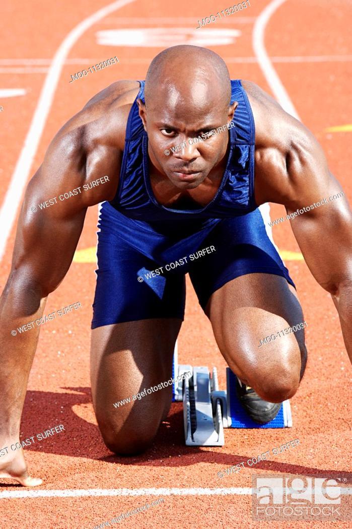 Stock Photo: Track Athlete on starting block.