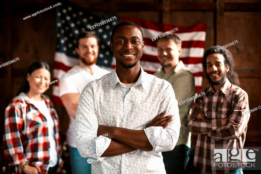 Photo de stock: American Group Of Staff Smiling Poses In The Interior Of Co-Working Spase Against The Backdrop Of A Wooden Wall With An American Flag.