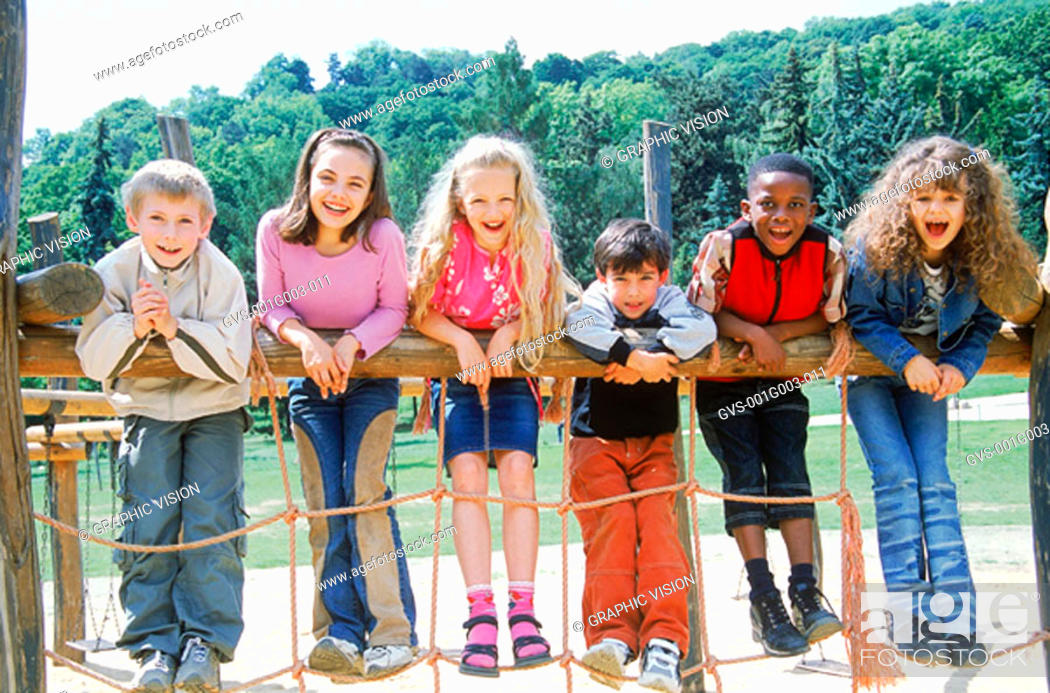 Stock Photo: Young children leaning on gate smiling.
