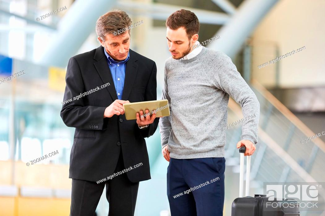 Imagen: Zwei Business Männer machen Terminplanung für die Geschäftsreise mit Tablet am Flughafen.