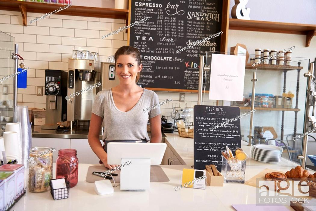 Stock Photo: Woman waiting behind the counter at a coffee shop, close up.