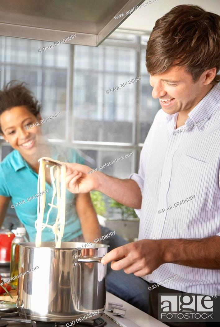 Stock Photo: Couple cooking meal in kitchen.