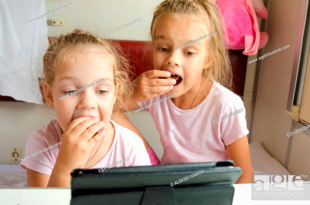 Stock Photo: Two girls sisters sitting in the train watching cartoon Tablet PC.