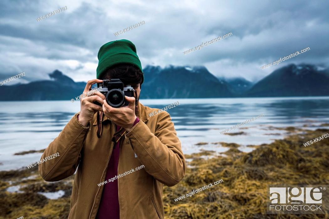 Stock Photo: Young man with woolly hat taking pictures with camera.