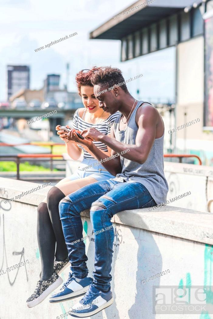 Stock Photo: Couple in urban area looking at smartphone, Milan, Italy.