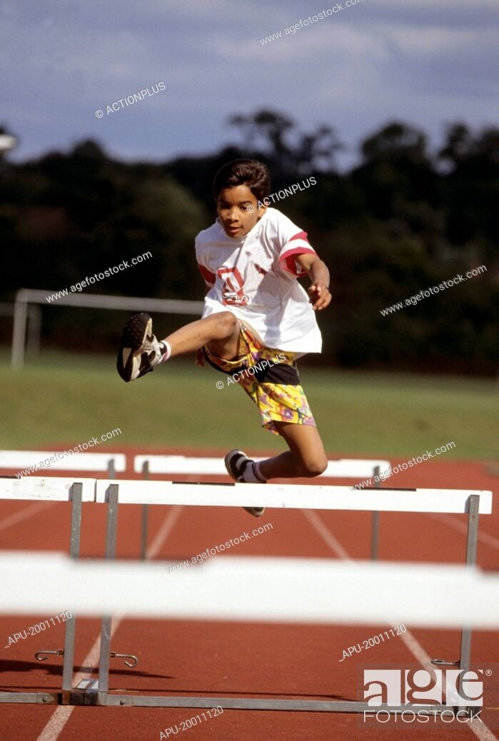 Stock Photo: Boy jumping over hurdles on track.