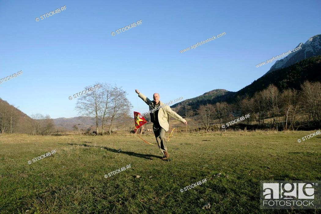 Stock Photo: Mature man running over a meadow with a kite.