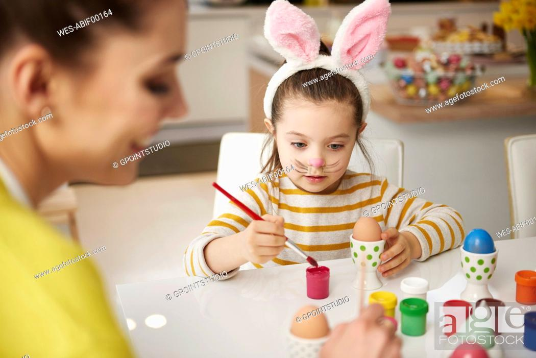 Stock Photo: Mother and daughter with bunny ears sitting at table painting Easter eggs.