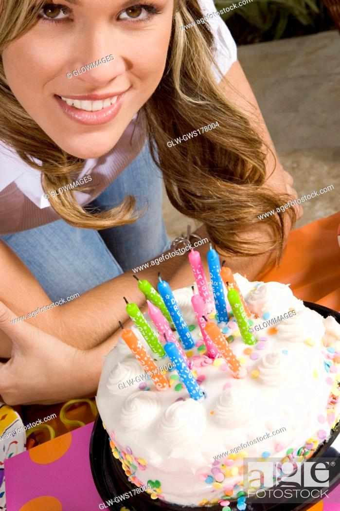 Stock Photo: Portrait of a young woman standing in front of a birthday cake and smiling.