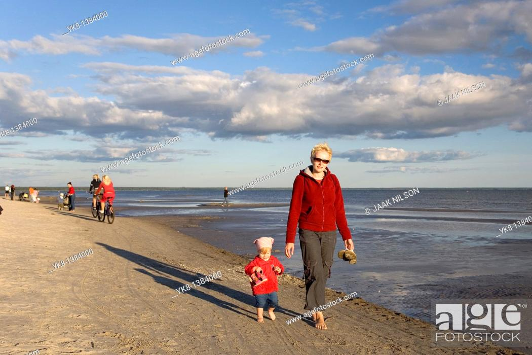 Stock Photo: Woman with Kid in Red Clothes Walking Hand in Hand on Pärnu Beach in Estonia, Europe.