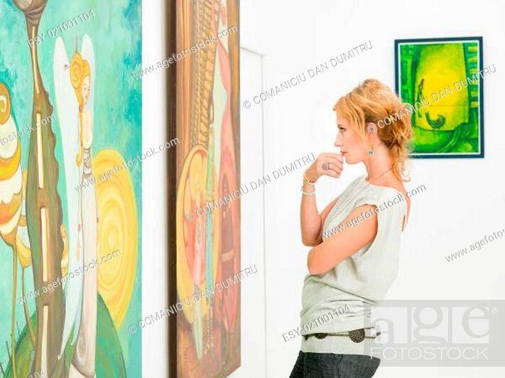 Imagen: woman contemplaing colorful paintings.