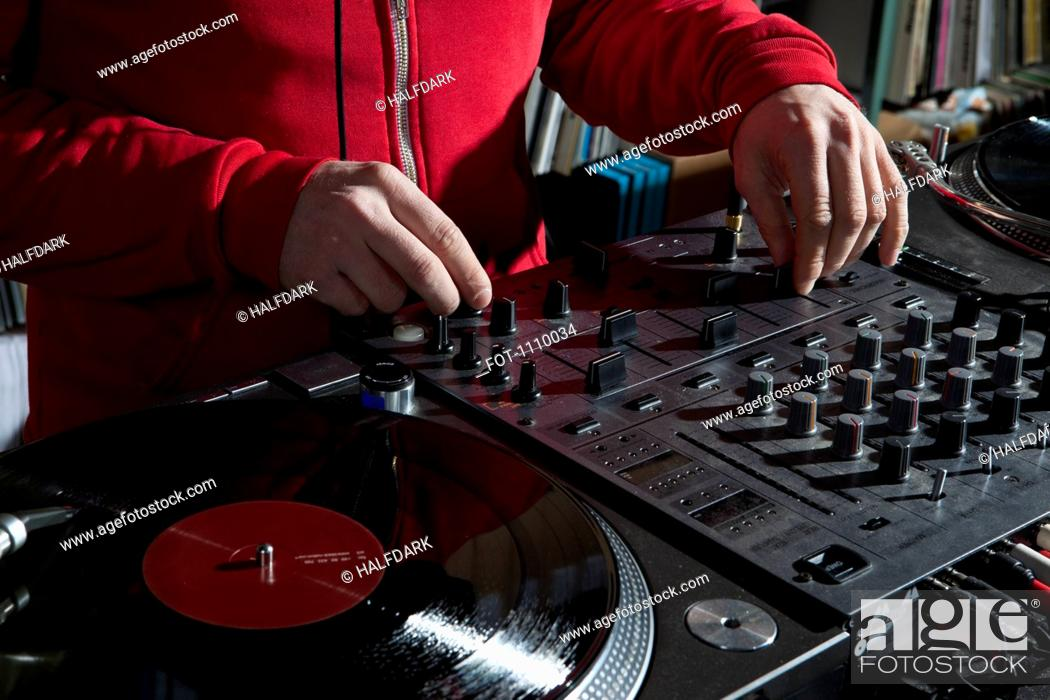 Stock Photo: A DJ adjusting knobs on a sounder mixer, detail of hands.