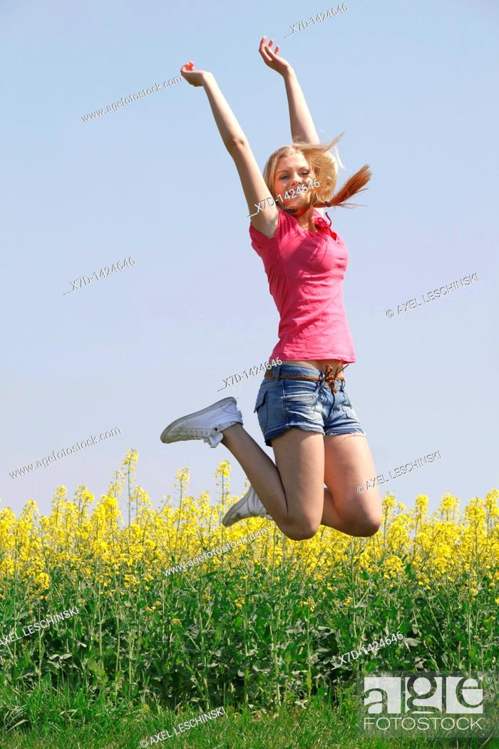 Stock Photo: young blonde woman enjoying a walk in spring landscape jumping in the air.