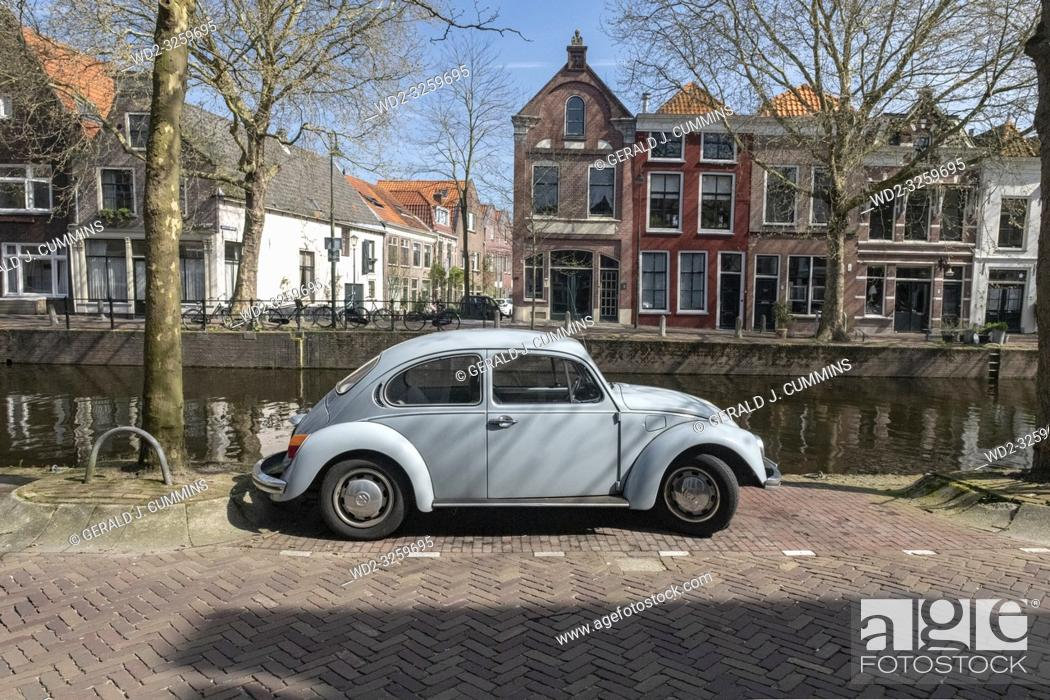 Stock Photo: Netherlands, Gouda, 2017, An old volkswagen beetle, parked along the side of a canal or grachten. In the background the typical architecture of the city can be.