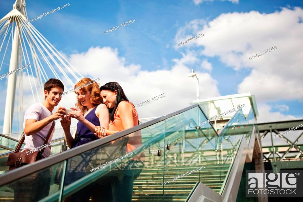 Stock Photo: Three people looking at a mobile phone on Hungerford Bridge, London.