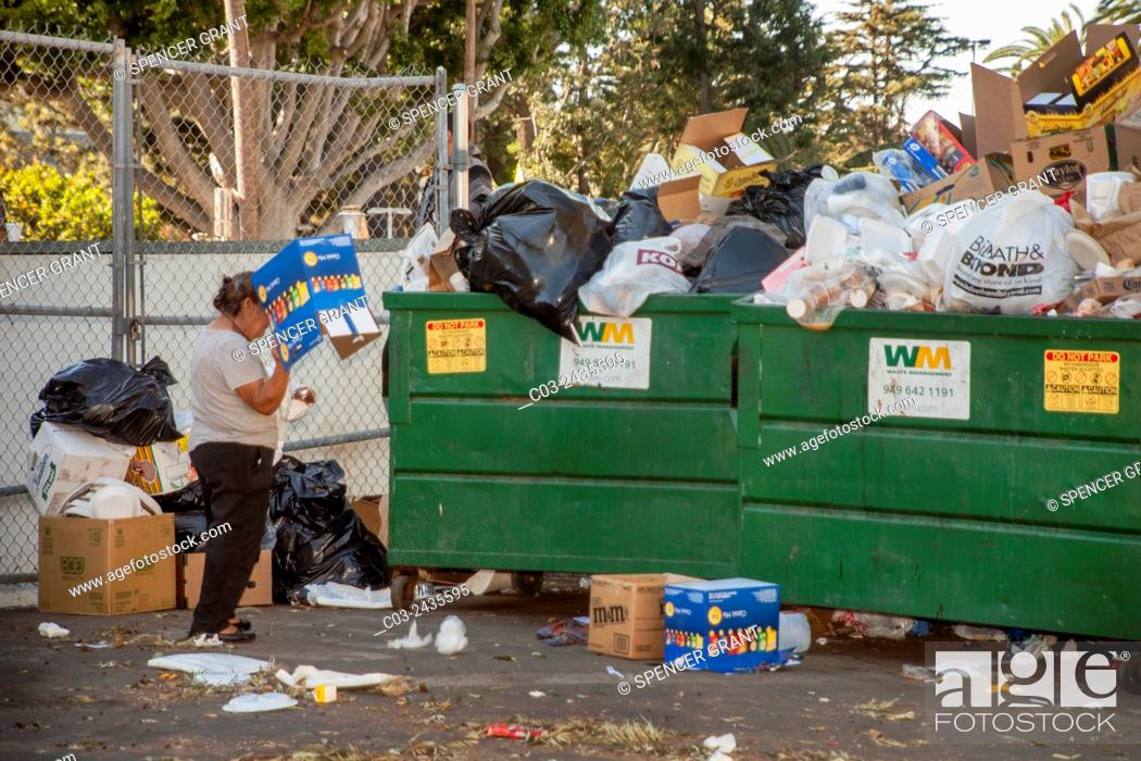 Stock Photo: A Hispanic woman searches a dumpster for items of value in Santa Ana, CA.