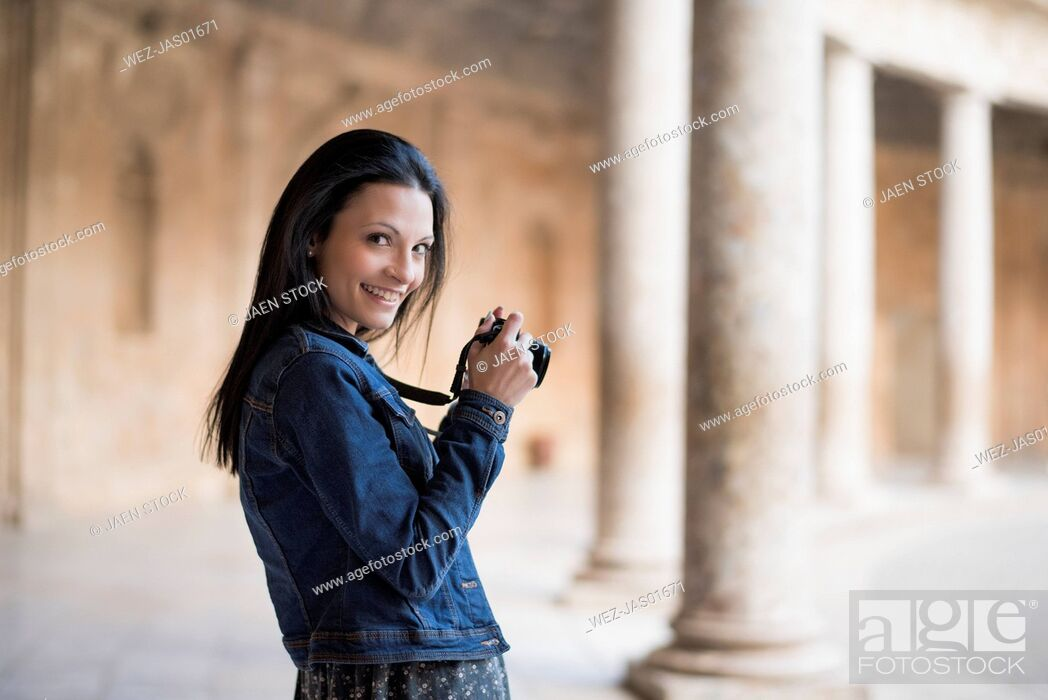 Stock Photo: Spain, Granada, smiling young woman with camera at the Alhambra.