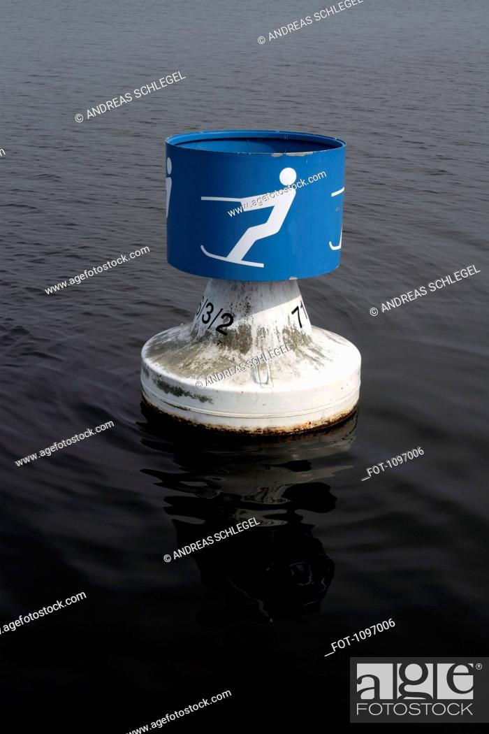 Stock Photo: A buoy with a symbol for waterskiing on a lake.