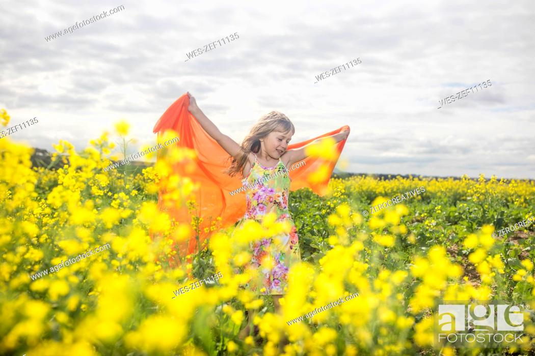Stock Photo: Little girl with orange cloth standing in rape field.