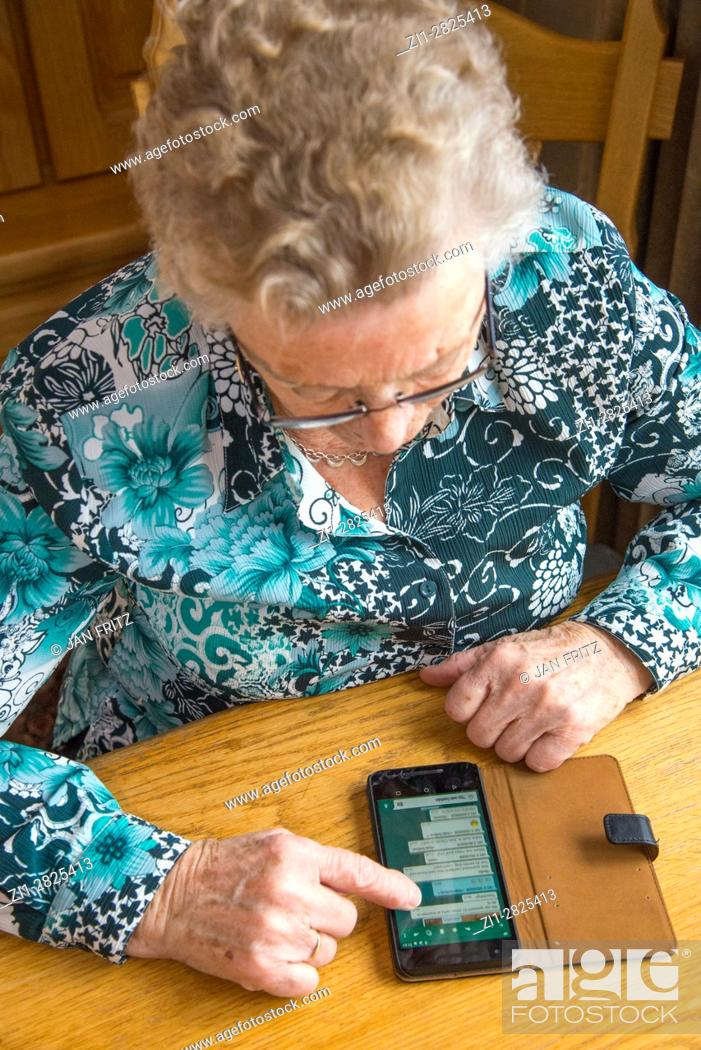 Stock Photo: old woman at table with smartphone.