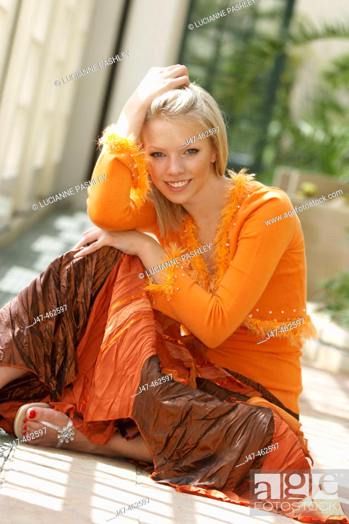 Stock Photo: 21 year old girl sitting on the floor, smiling into camera.