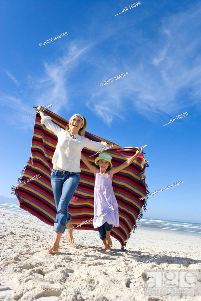 Stock Photo: Mother and daughter 5-7 holding up blanket on beach, smiling, low angle view.