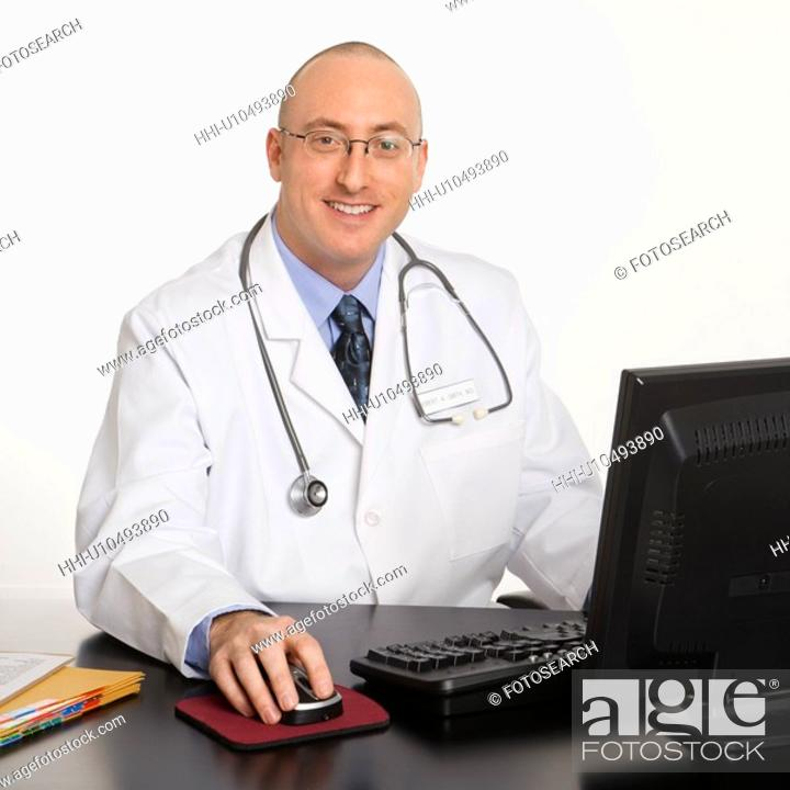 Stock Photo: Caucasian mid adult male physician sitting at desk with laptop computer.