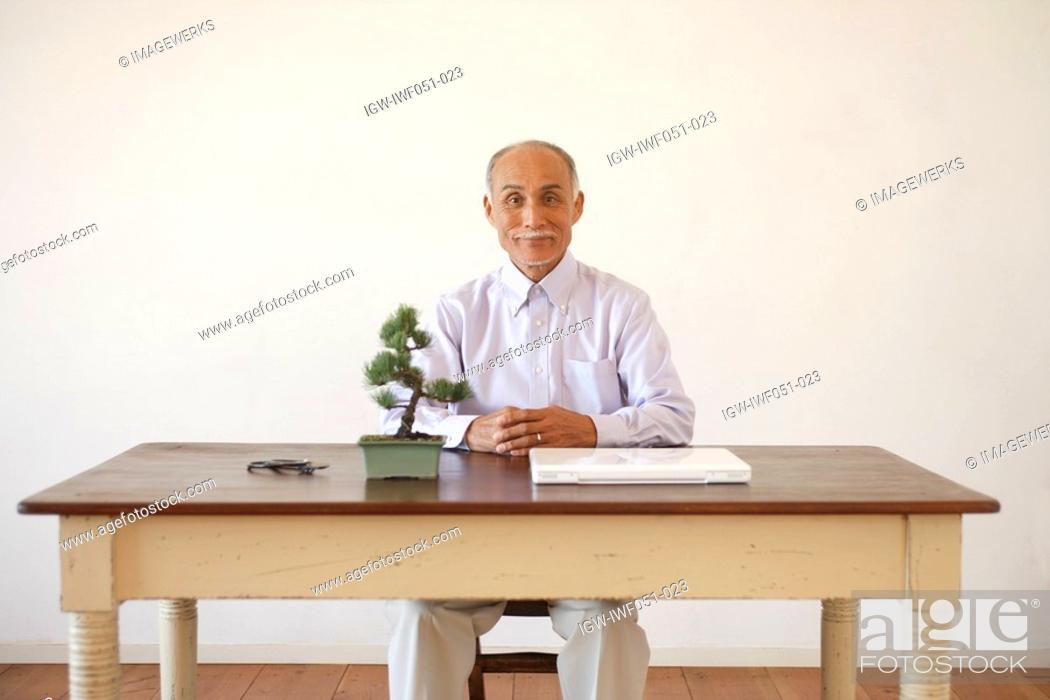 Stock Photo: Senior man sitting by table and potted plant.