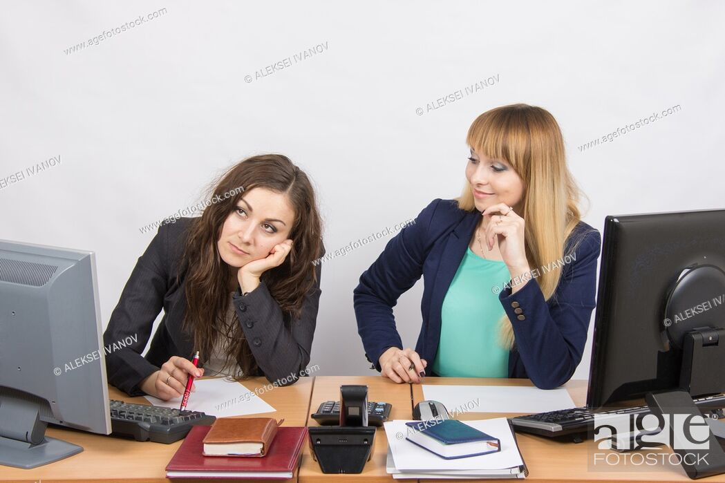 Stock Photo: Two young beautiful girls colleagues sitting at the same desk in the office.