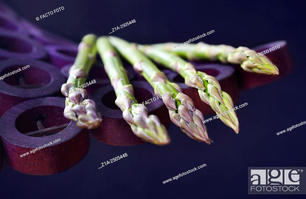 Stock Photo: Five green asparagus on a violet holder on dark blue background.