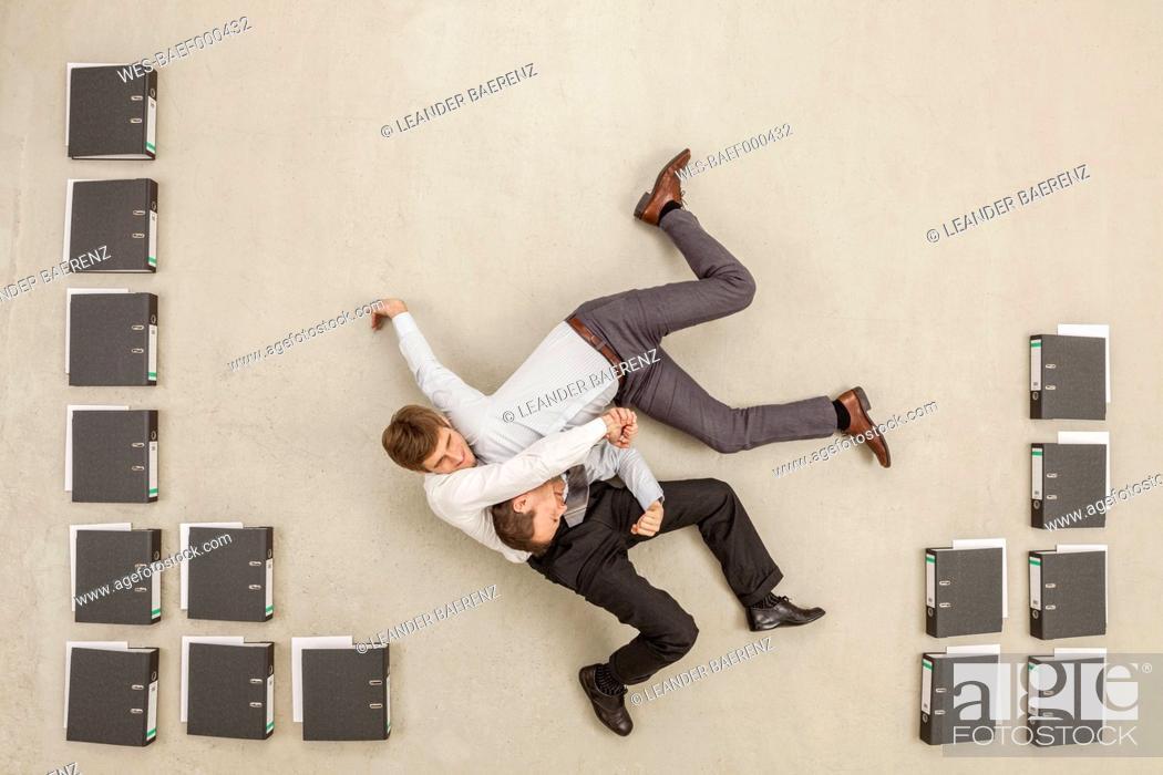 Stock Photo: Businessmen fighting in office between files.