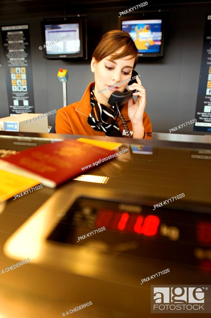 Stock Photo: Female airline check-in attendant talking on the telephone.