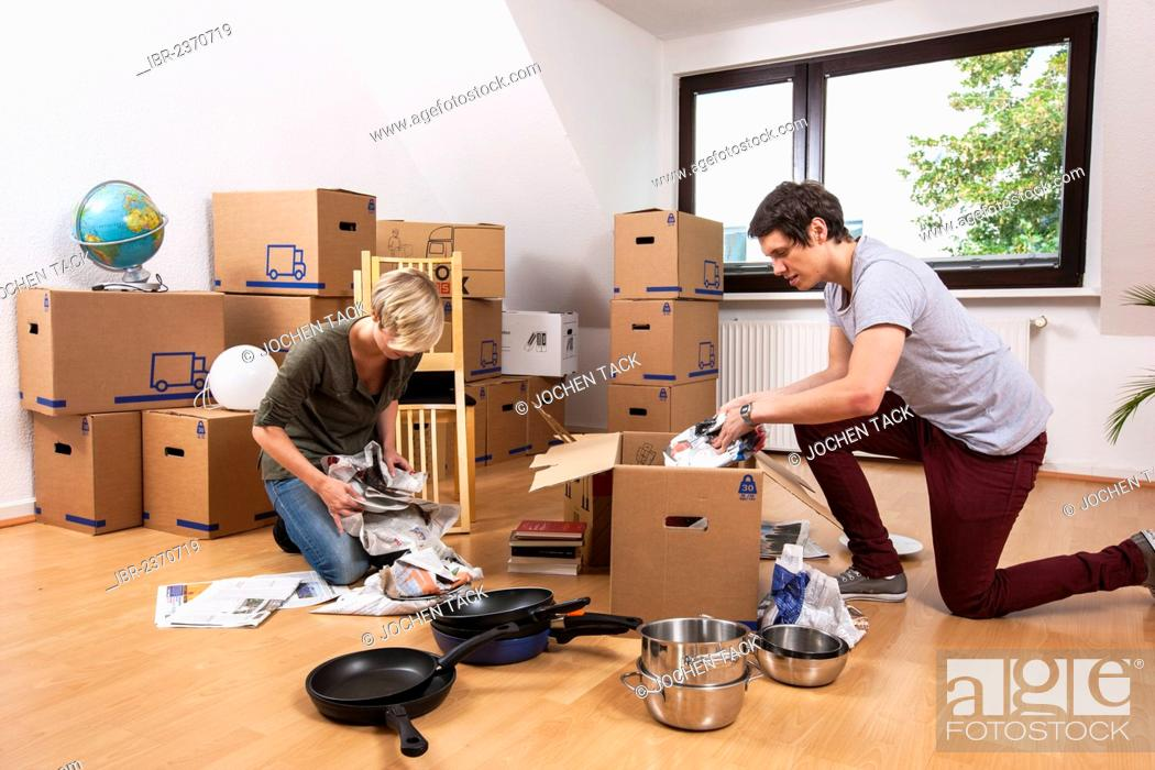 Stock Photo: Young couple in an empty room in a new apartment unpacking the first boxes.