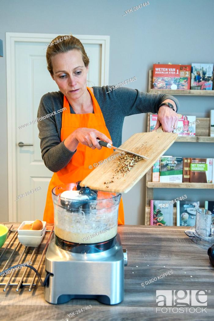 Stock Photo: Kaatsheuvel, Netherlands. Mid adult caucasian woman preparing to bake a cake inside her residential kitchen.