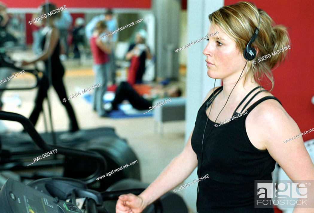 Stock Photo: Young woman at the gym, fitness center, walking on the treadmill.