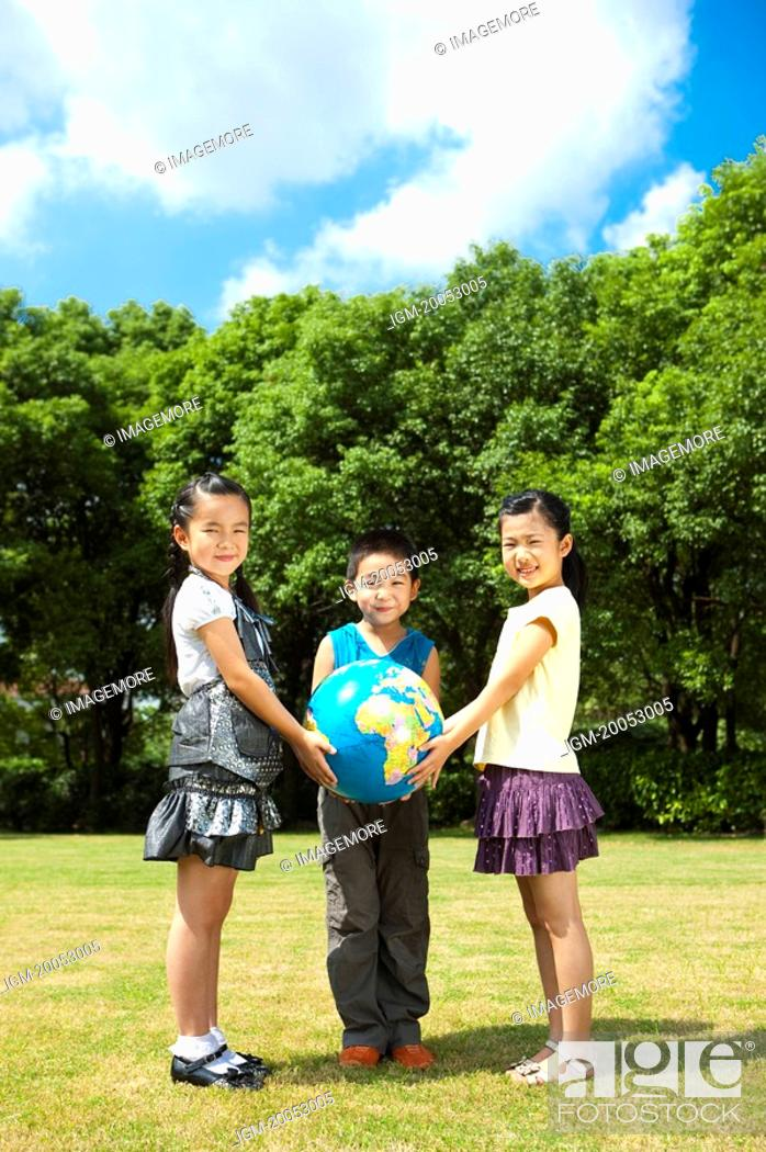 Stock Photo: Three children holding the globe together and looking at the camera with smile.