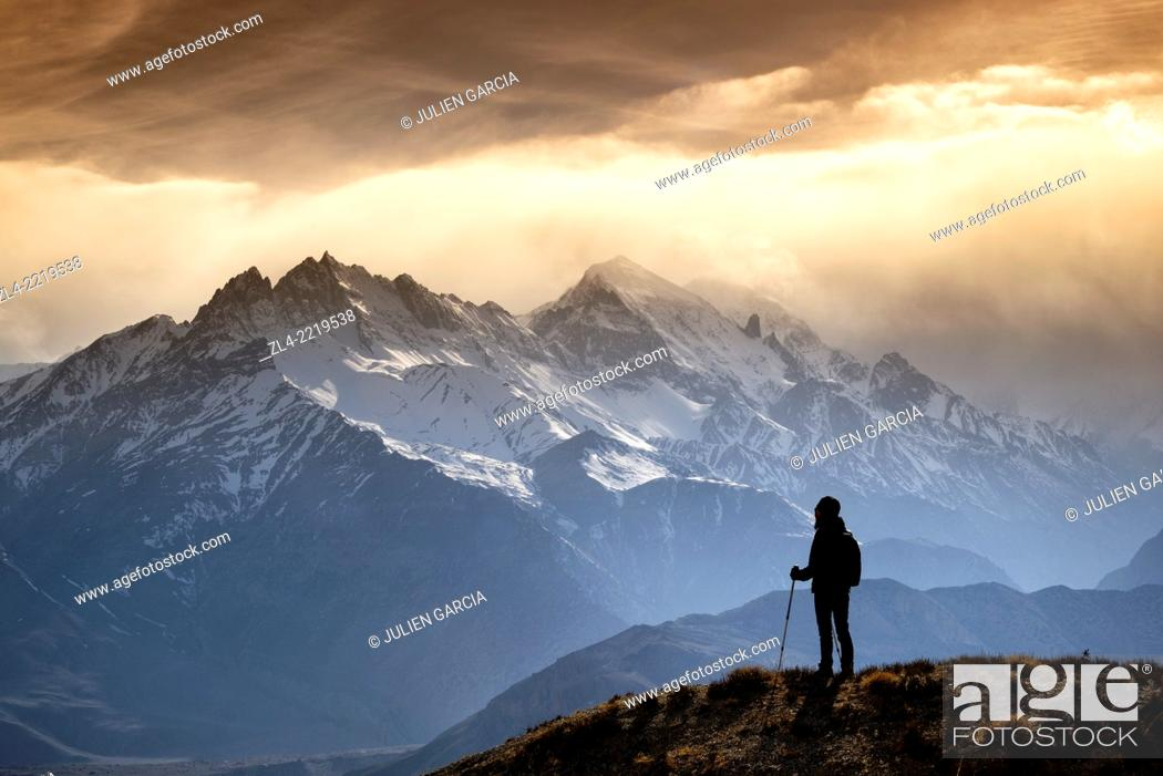 Stock Photo: Silhouette of a trekker watching the mountains in the evening sun light. Nepal, Gandaki, Upper Mustang (near the border with Tibet). Model Released.
