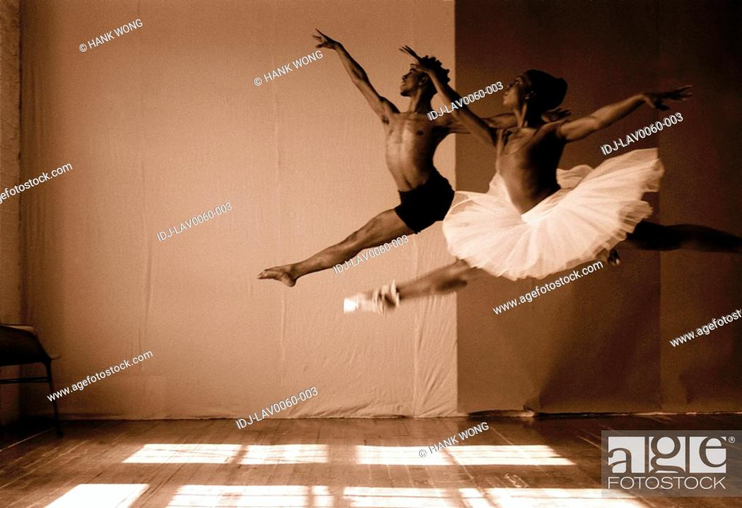 Stock Photo: Male and female ballet dancers jumping in a studio.