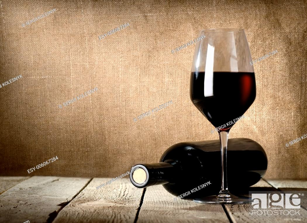 Stock Photo: Black bottle of wine and wneglass on the background of the canvas.