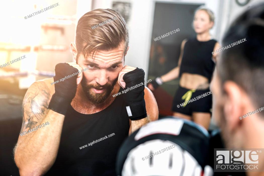 Stock Photo: Boxer sparring with coach.
