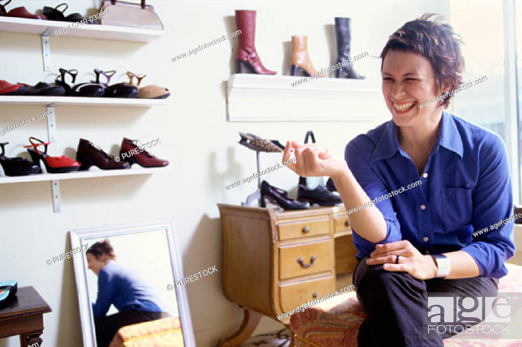 Stock Photo: Young woman sitting in a shoe store.