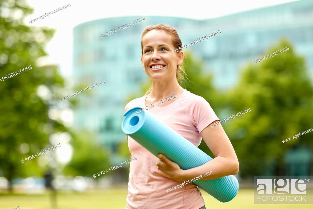 Photo de stock: happy smiling woman with exercise mat at city park.