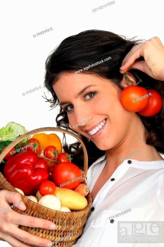 Stock Photo: Brunette holding vegetables.